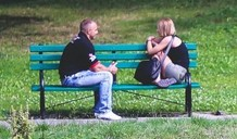 Two people talking on a bench.