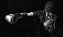 A black and white image of a man boxing.