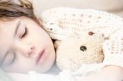 child asleep with bear
