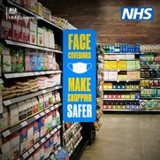 A supermarket aisle with a sign saying face coverings make shopping safer