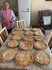 Flo standing next to the freshly baked pies she baked for her community