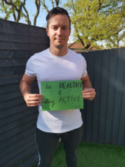 personal trainer Ant holding a sign saying 'be healthy & stay active'