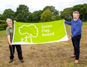 a man and a woman holding a green flag at thornbury country park