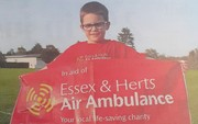 Tom aged 6 holding a sign saying 'Essex and Herts Air Ambulance'