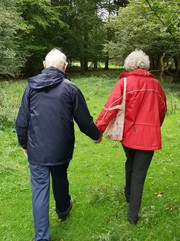 Two elderly people holding hands while walking in the countryside