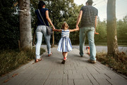 Two parents holding the hands of their young child while walking through a park
