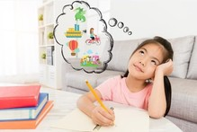 A child writing on a piece of paper with a thought bubble above their head imagining fun activities.