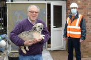 An Essex resident and his dog and a man in a high-vis vest standing in front of building works outside his home