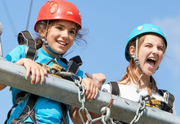 Two young girls wearing helmets on the high ropes at Essex Outdoors