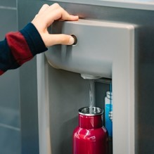 Child refilling metal water bottle from machine