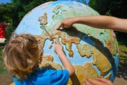child pointing at world