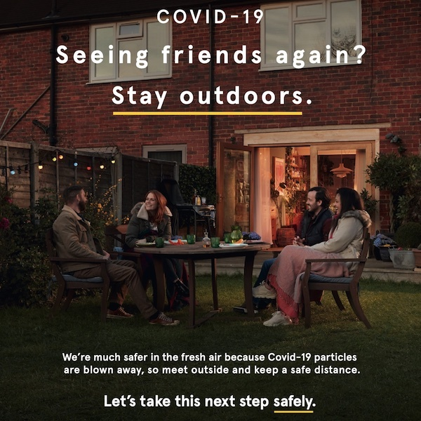 Covid19 poster of people sitting outside in a back garden at night