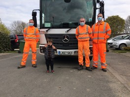 Theo stands at the front of the bin truck with three crew members and gives the camera a thumbs up