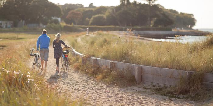 VIOW - couple walking bikes on the beach