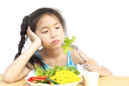 Asian girl showing bored expression with plate of vegetables and glass of milk