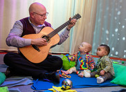bald man wearing glasses playing a guitar to 2 toddlers.