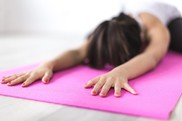 image of a woman doing yoga on a pink yoga mat