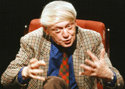 photo of Anthony Burgess siting in an armchair talking and gesturing with his hands