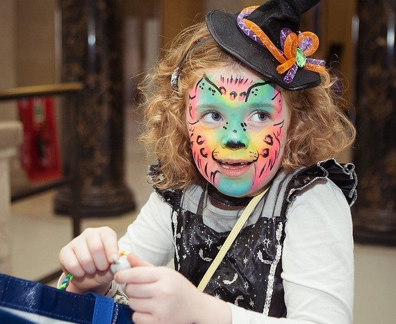 Young girl in witch dress up and face painted