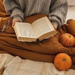 Reading book under blanket and pumpkins
