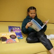 Girl reading book on yellow sofa
