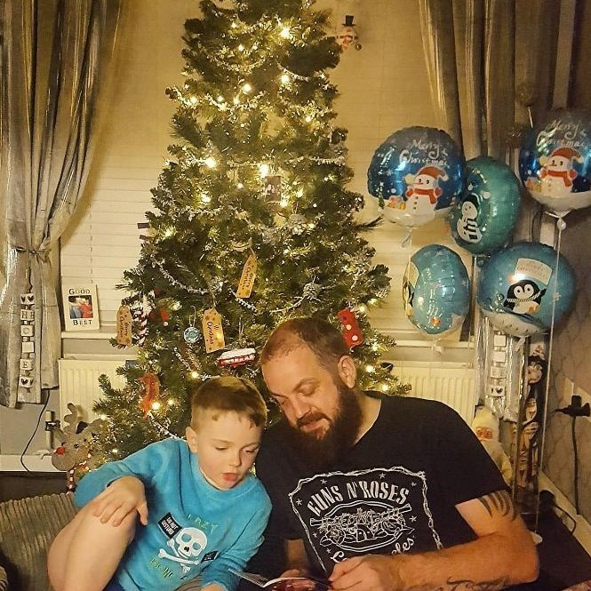 Boy and Dad reading Christmas tree
