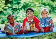 Three children smiling reading books