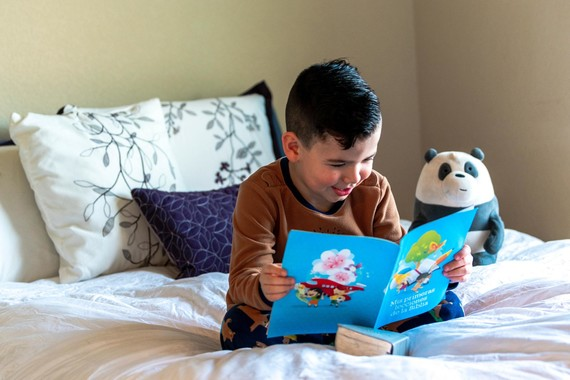 Boy reading a book sat on a bed