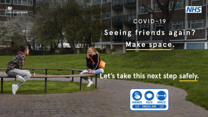 TEXT: COVID-19. Seeing friends again? Make space. Let's take this next step safely. PHOTOGRAPH: two friends sat on a bench outside residential flats