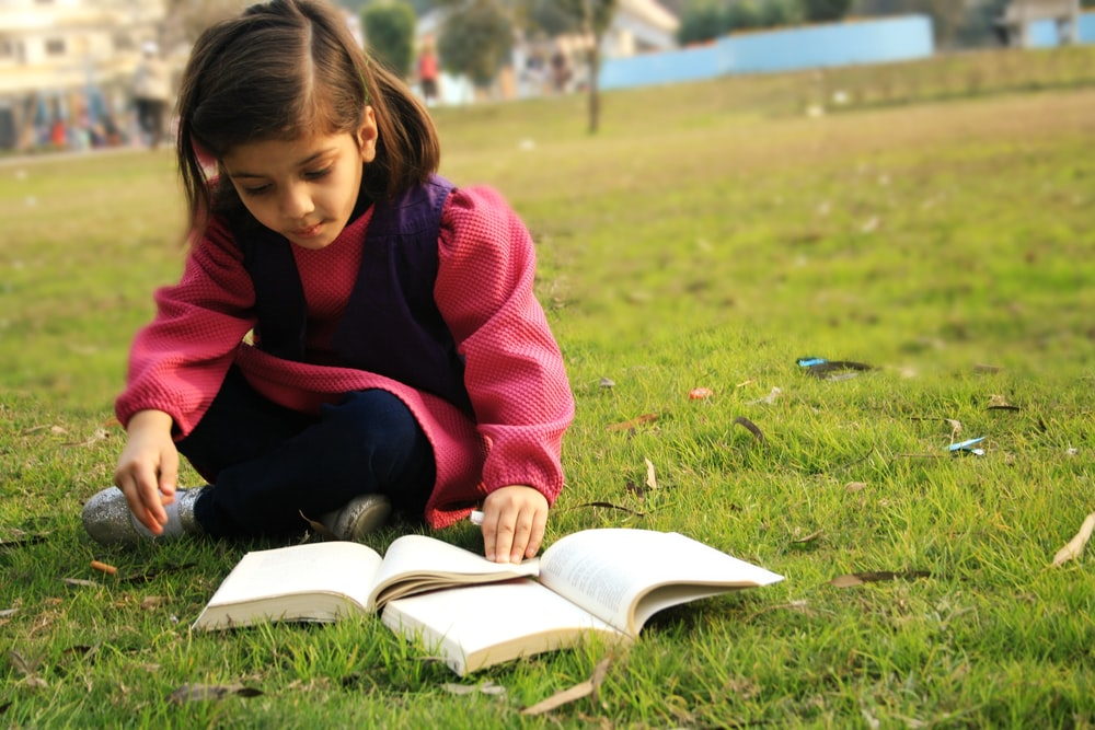 Child reading a book in a park