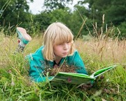 Child reading a book lying in a grassy field