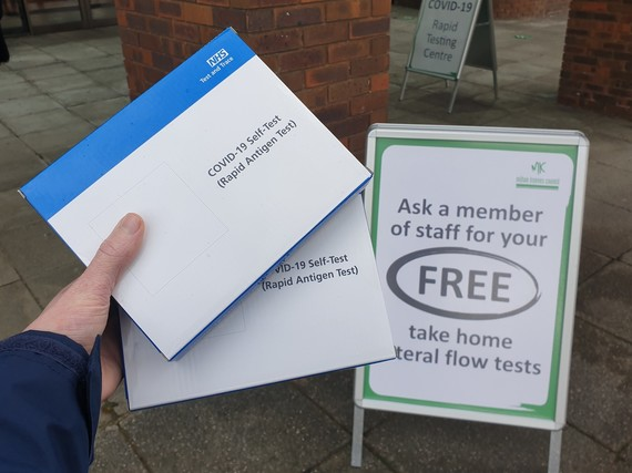 Photo of someone holding boxes of NHS COVID-19 rapid lateral flow tests