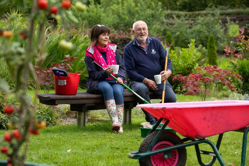 Older couple sat on bench in garden with mug cup of tea