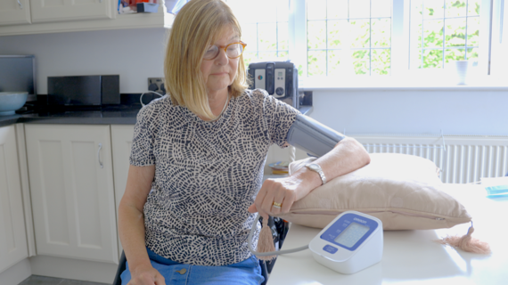 A lady taking her blood pressure at home