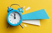 Blue ringing alarm clock on yellow background