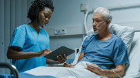A female nurse using an iPad talking to a male patient in bed