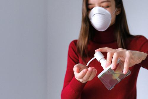 Woman wearing face mask applying hand sanitiser