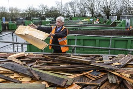 image of recycling centre staff putting cardboard in a container