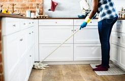 person cleaning kitchen floor with a mop