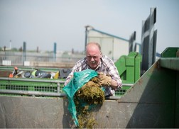 Resident emptying grass cutting into container at recycling centre