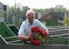 man emptying garden waste into container at recycling centre