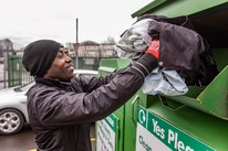 man emptying recycling of textiles are clothes bank at recycling centre