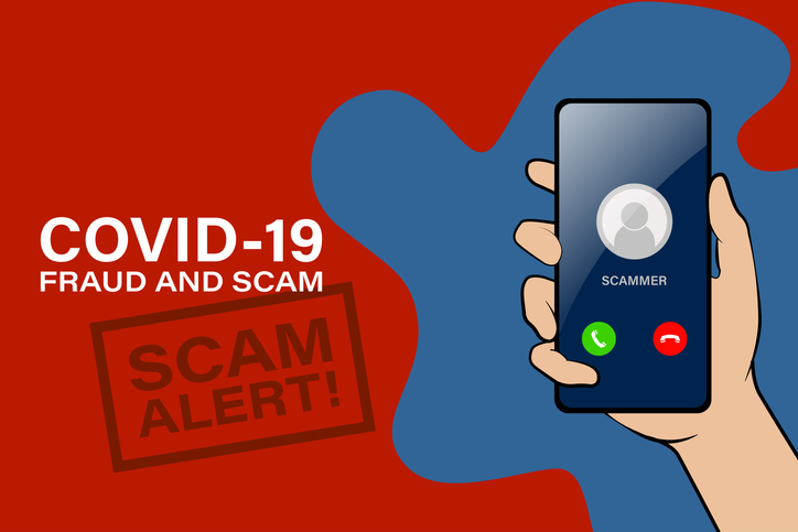 Hand holding phone with COVID-19 scam text