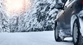 Image of car driving on a snowy road