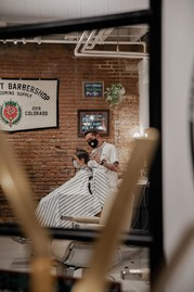 barbershop with customer and barber wearing PPE