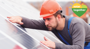 man on roof by solar panel