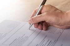 person with a pen completing a survey