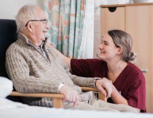 Elderly man with female carer