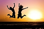 two young people jumping against a sunset background