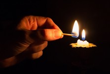 Hand holding a lighted match next to a candle which has almost burned out